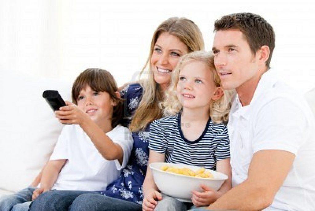 10246460-familia-sonriente-viendo-una-pelicula-en-television